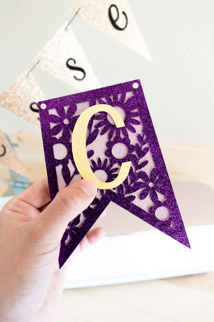 Holding a beautiful purple cut out banner made with Cricut