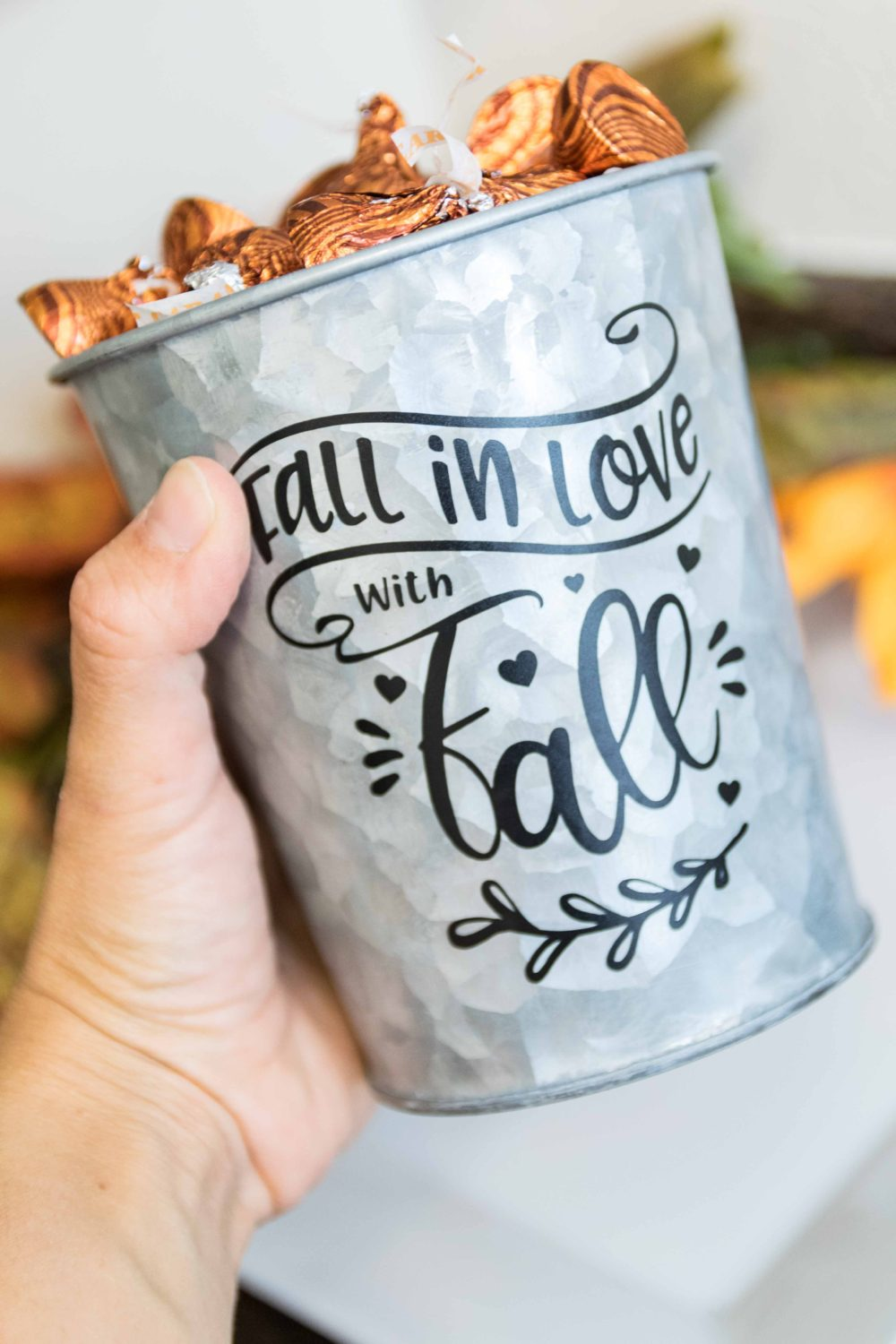 holding a fall-themed decorated candy bucket