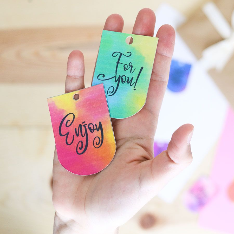 "Holding watercolor gift tags that say ""for you"" and ""enjoy"""