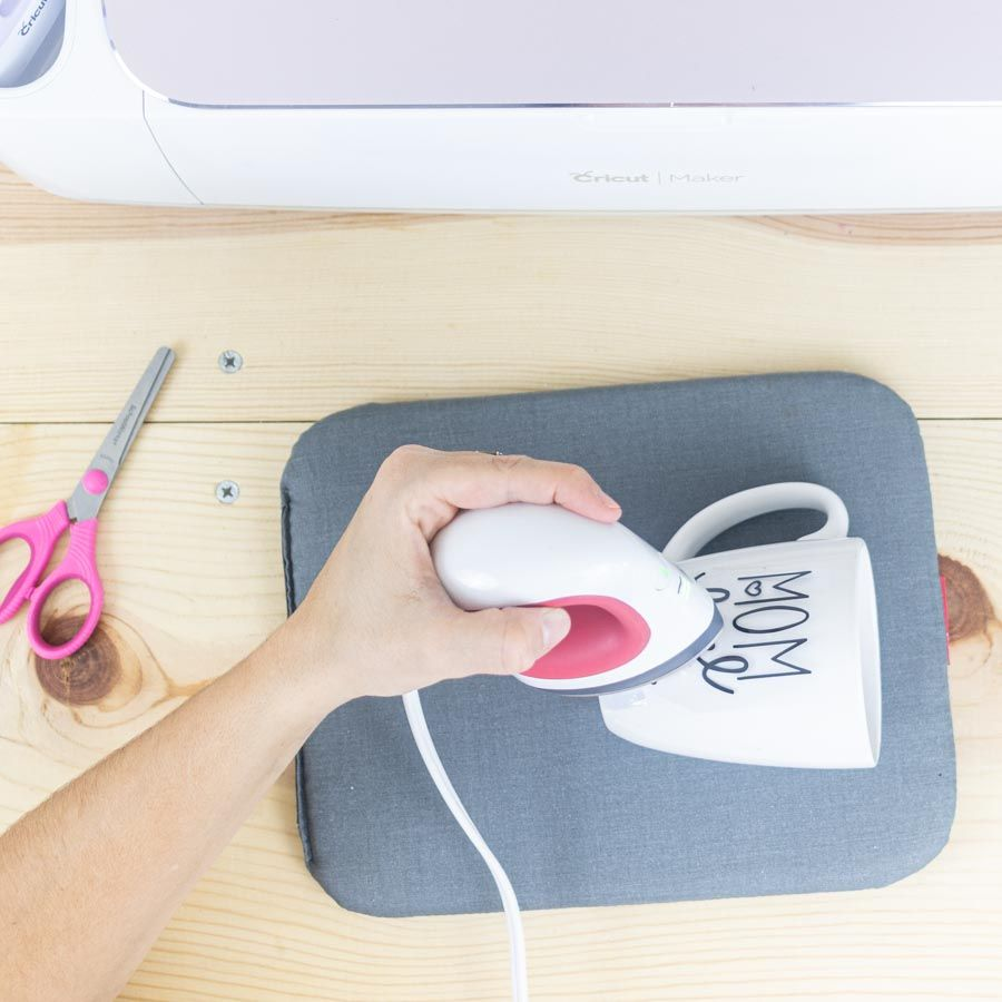 pressing iron-on on ceramic mug with HTV